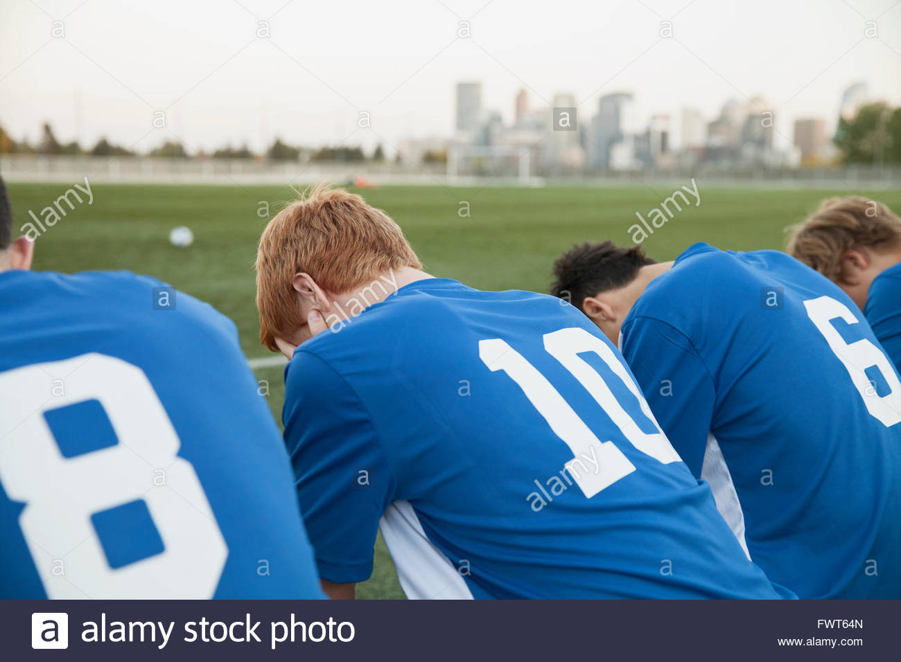 View from behind of soccer players on bench with heads bowed. - Stock Image