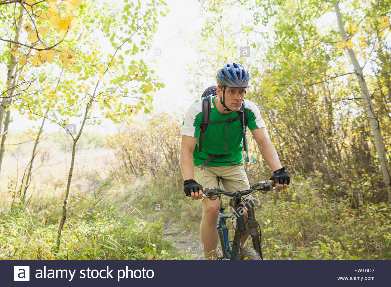 Man with serious look riding mountain bicycle. - Stock Image
