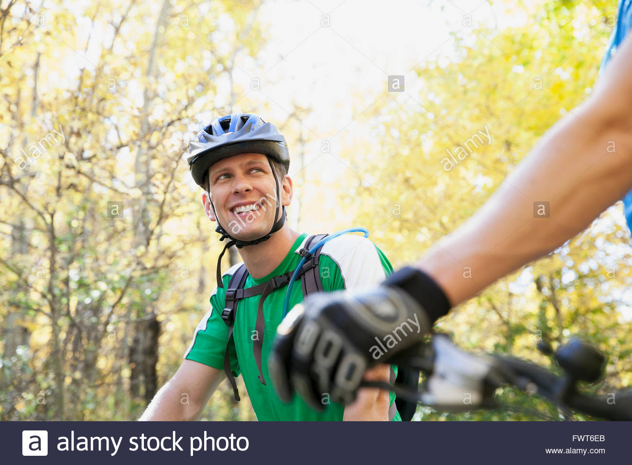 Man turning to look at biking partner. - Stock Image