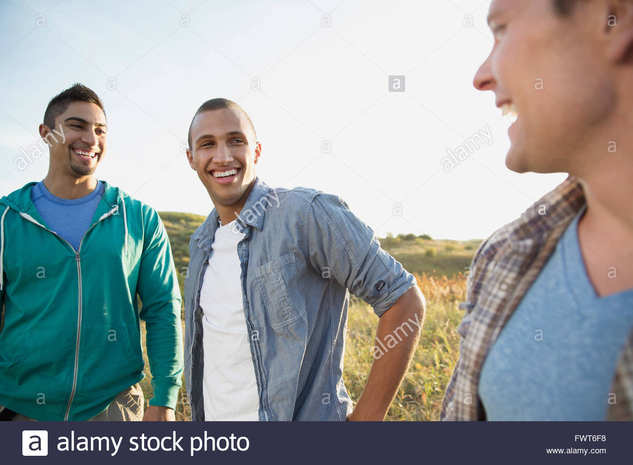 Three friends having a conversation outdoors. - Stock Image