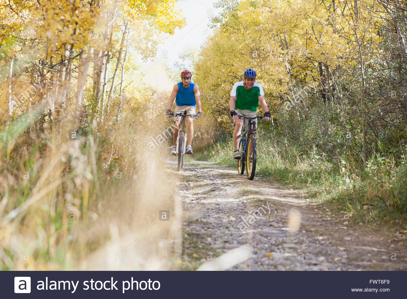 Men racing along path with their mountain bikes. - Stock Image