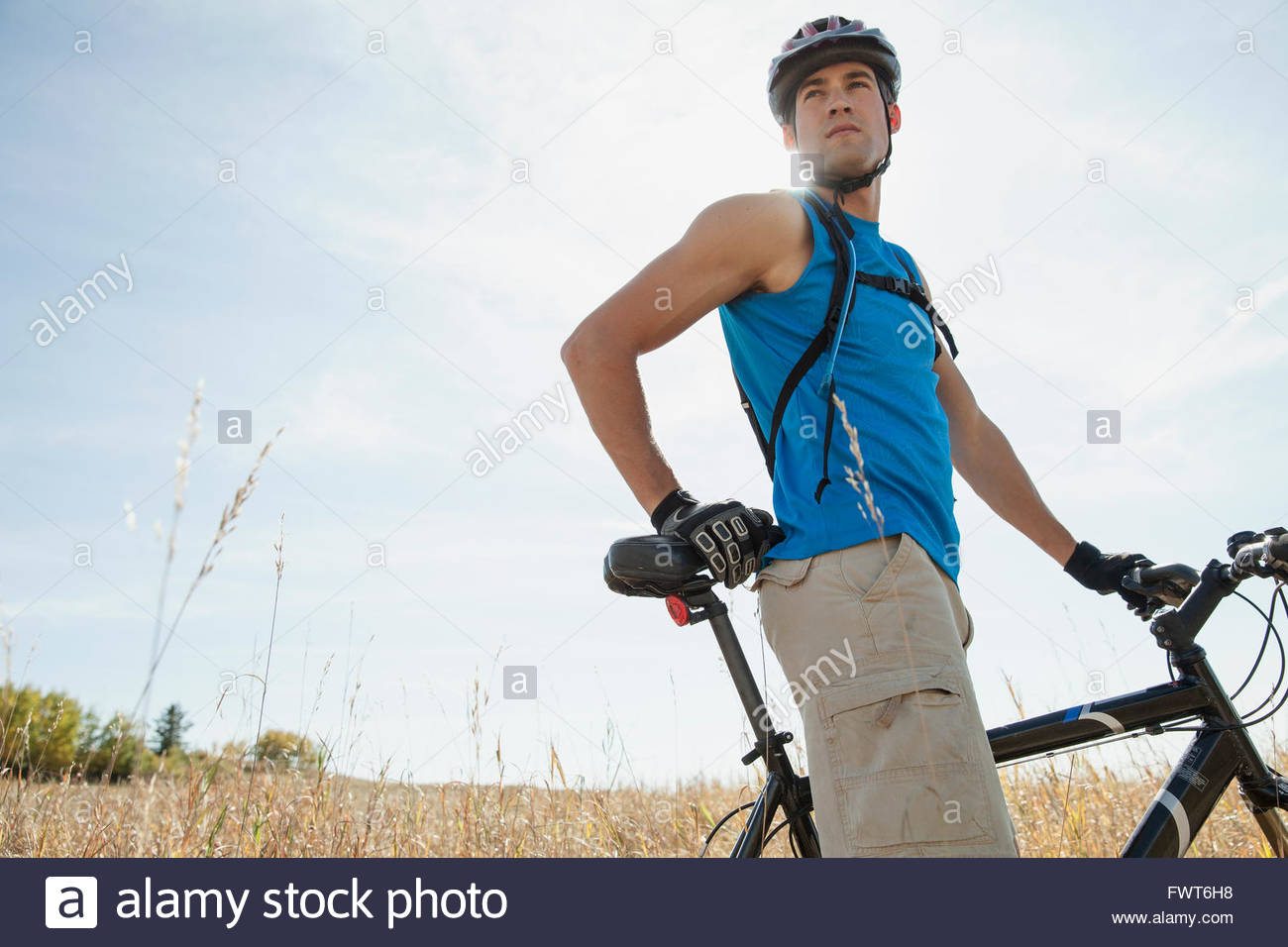 Young adult man with mountain bike in field. - Stock Image