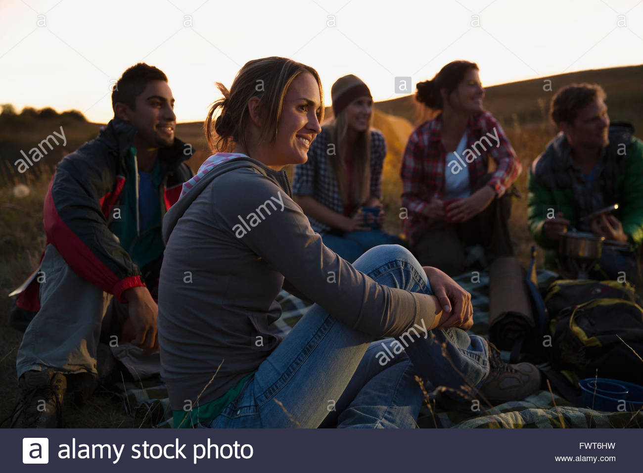Friends sitting outdoors at dusk. - Stock Image