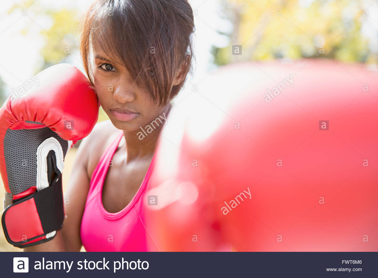Woman with boxing gloves doing outdoor workout. - Stock Image