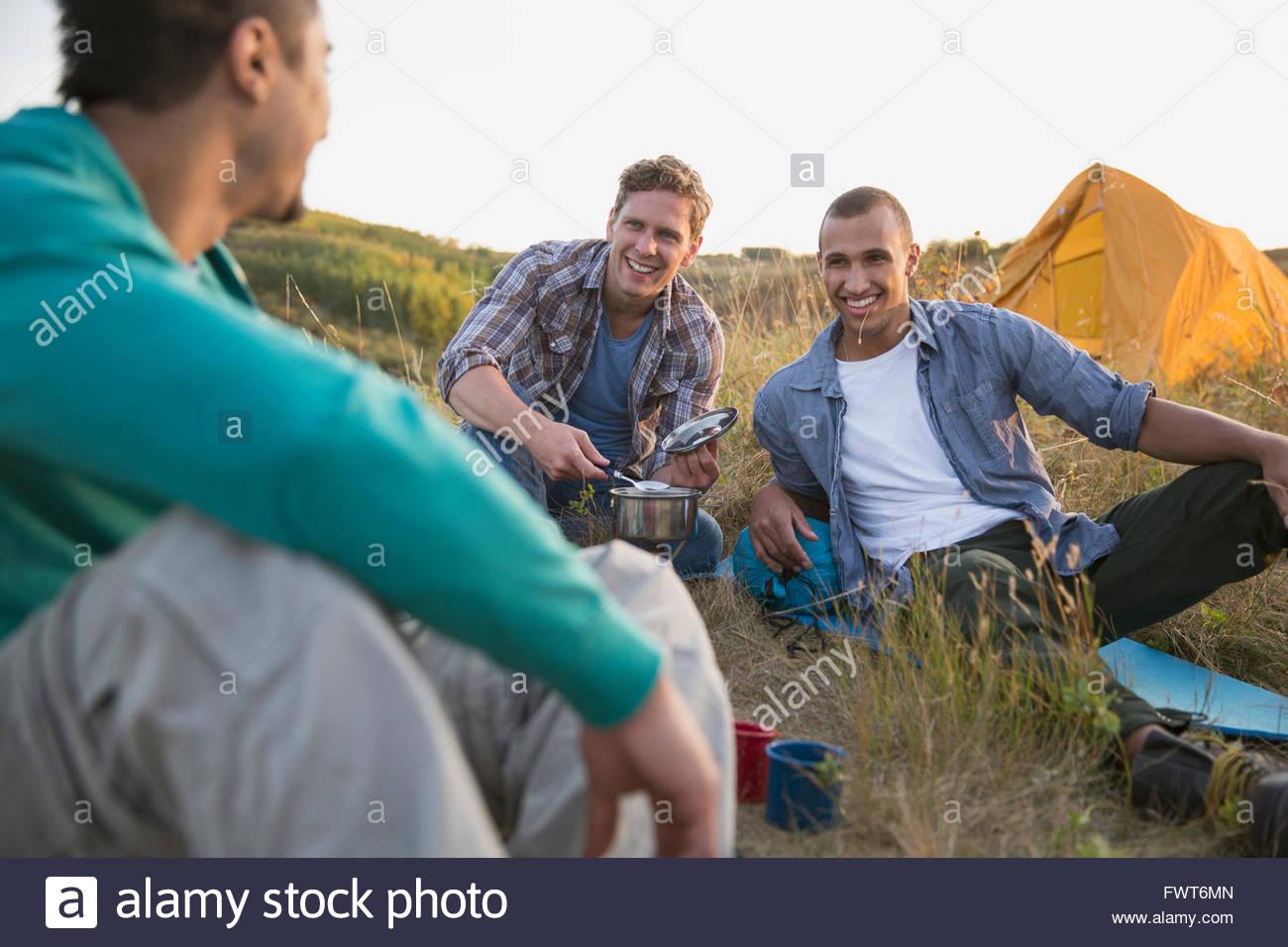 Three men sharing a laugh while camping. - Stock Image