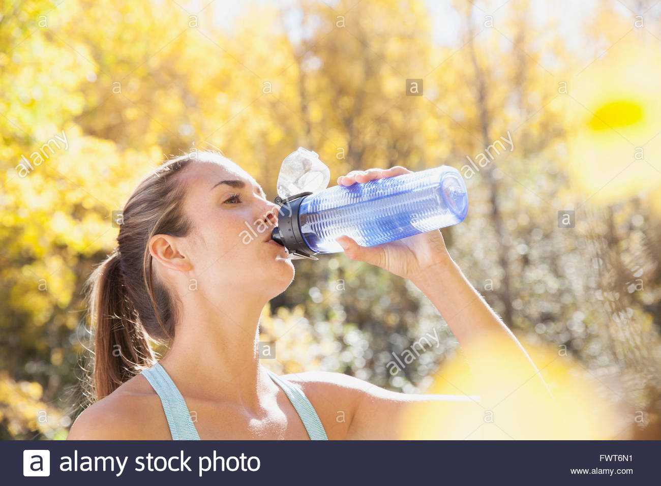 Woman stopping to drink some water outdoors. - Stock Image