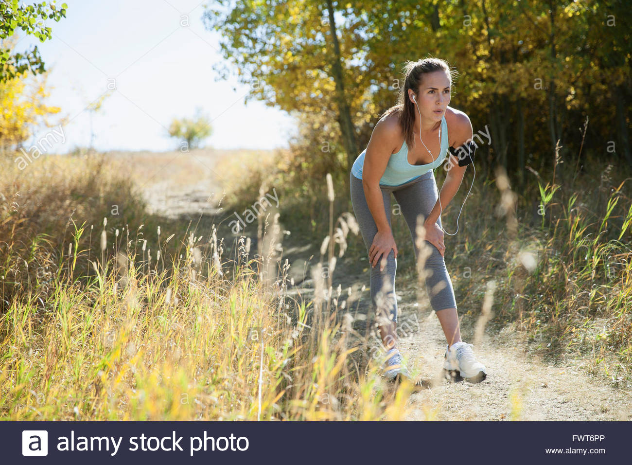 Woman stopping to stretch during outdoor run. - Stock Image