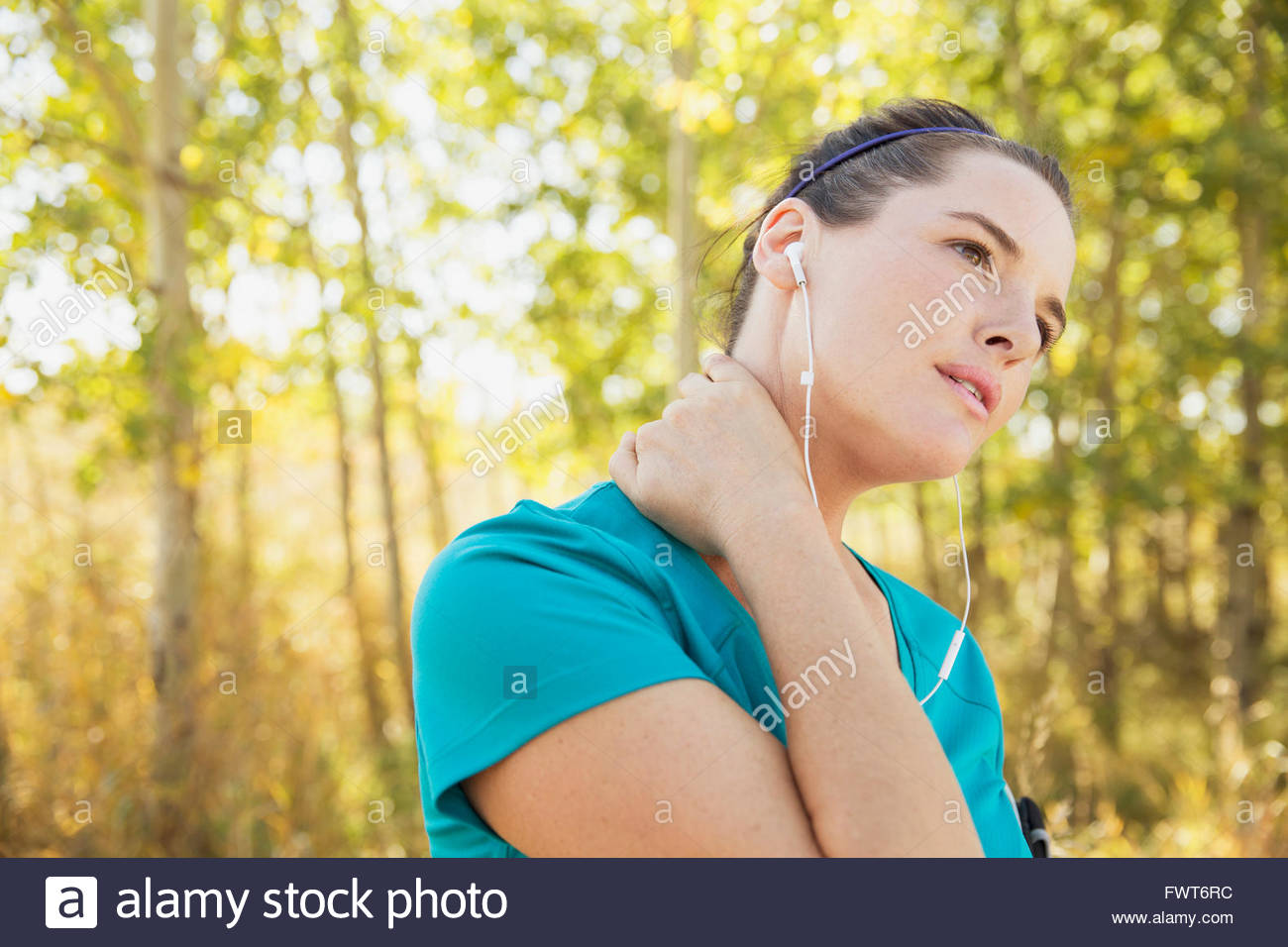 Runner with hand on her neck outdoors. - Stock Image