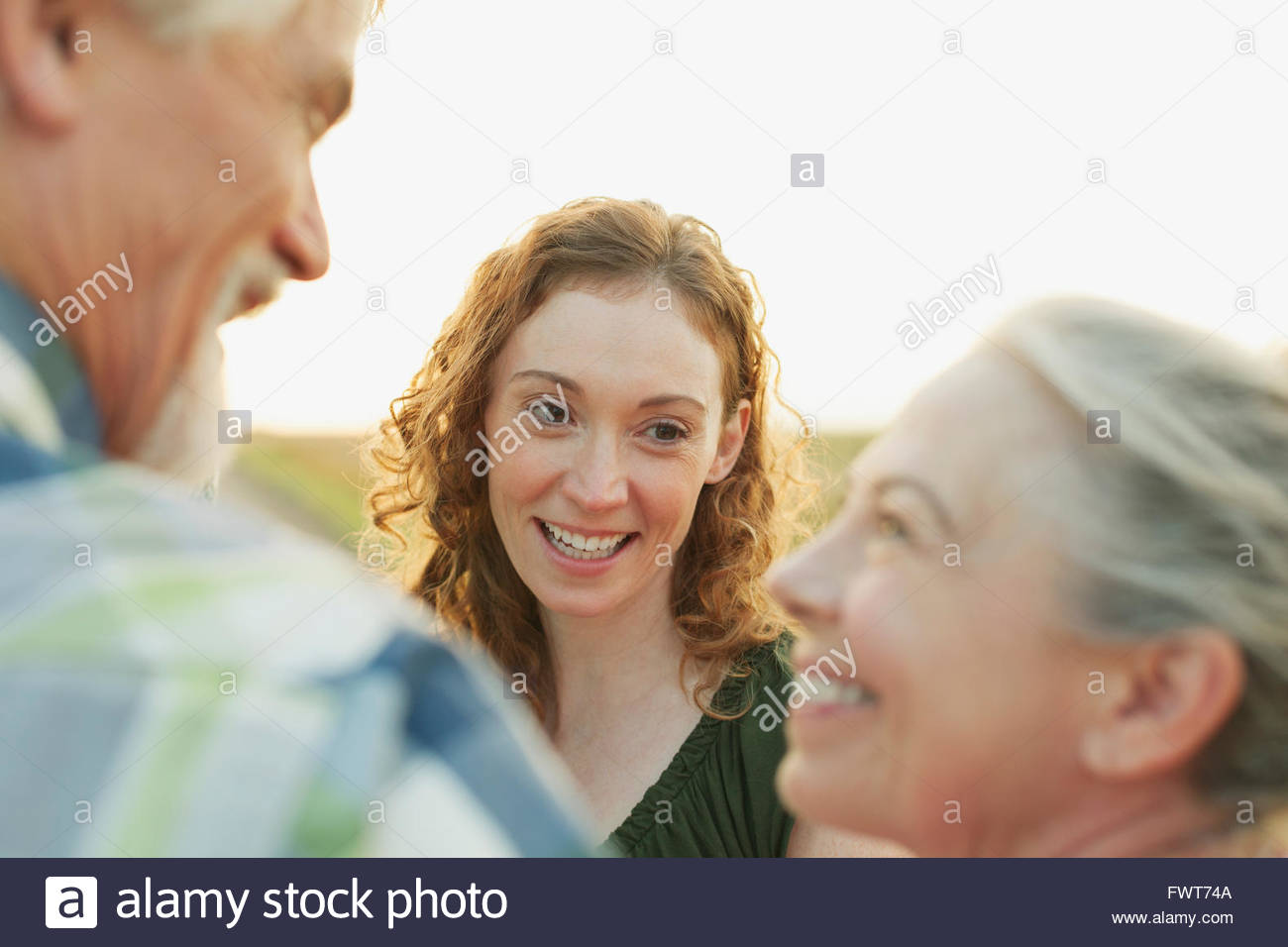Daughter talking with older parents outdoors. - Stock Image