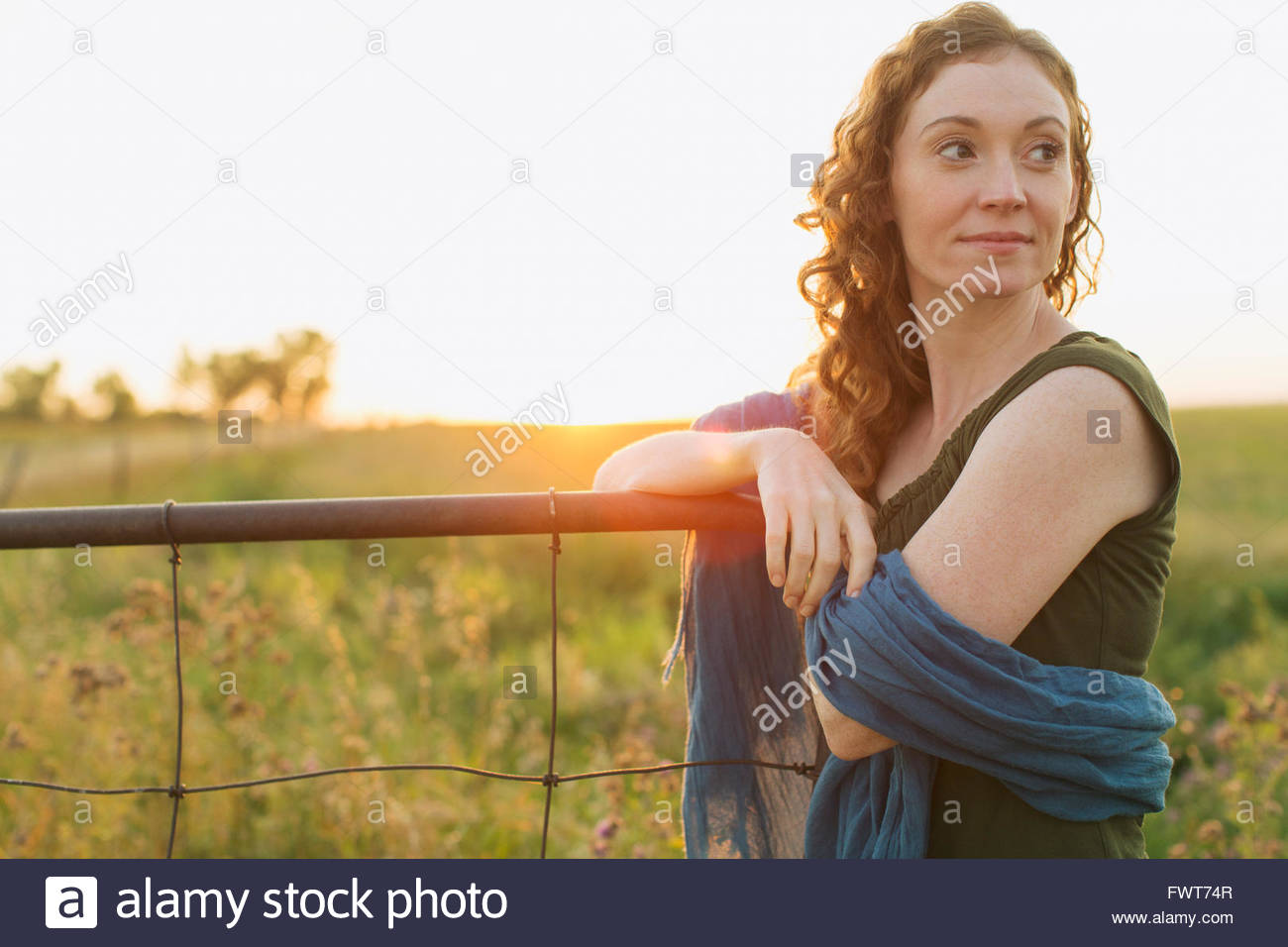 Pretty woman leaning on fence outdoors. - Stock Image