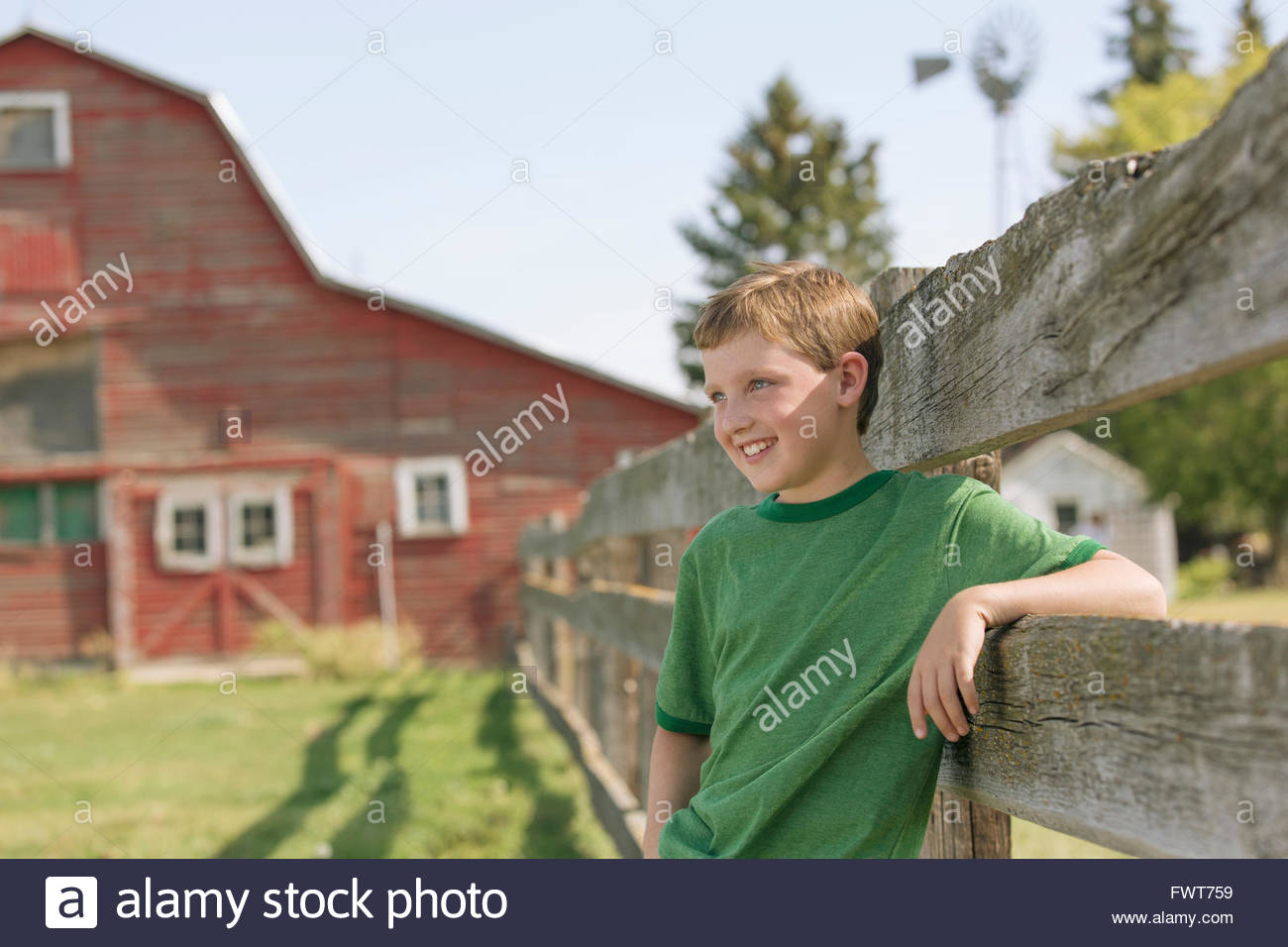 Young boy leaning on fence on rural property. - Stock Image