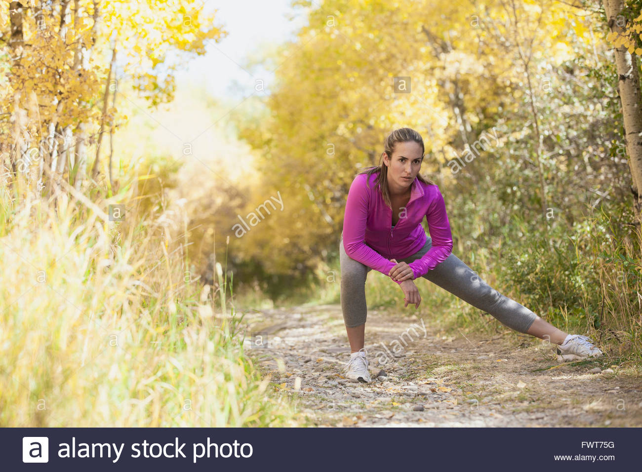 Woman stretching before outdoor run. - Stock Image