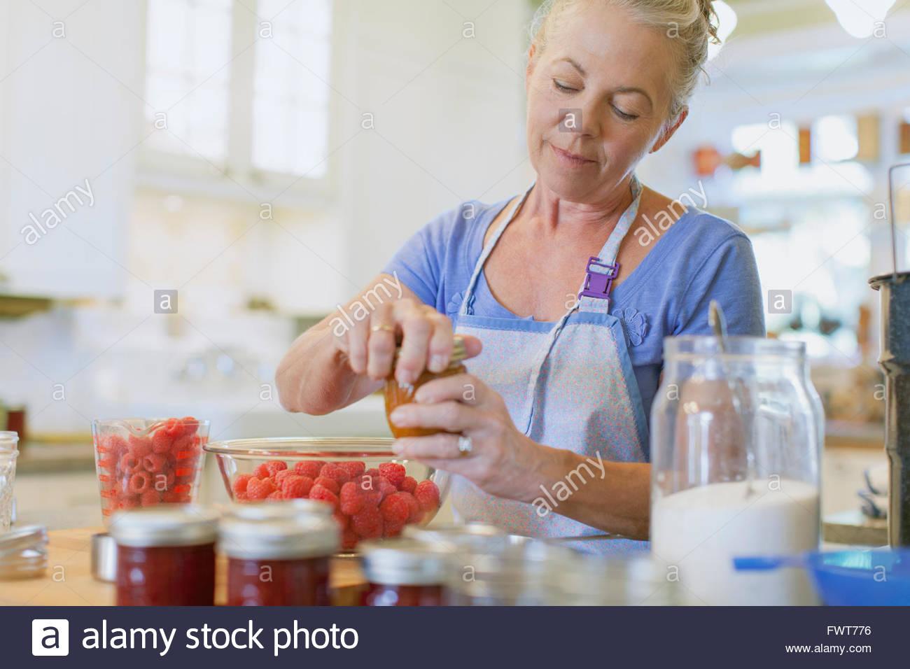 Woman making jam in kitchen. - Stock Image
