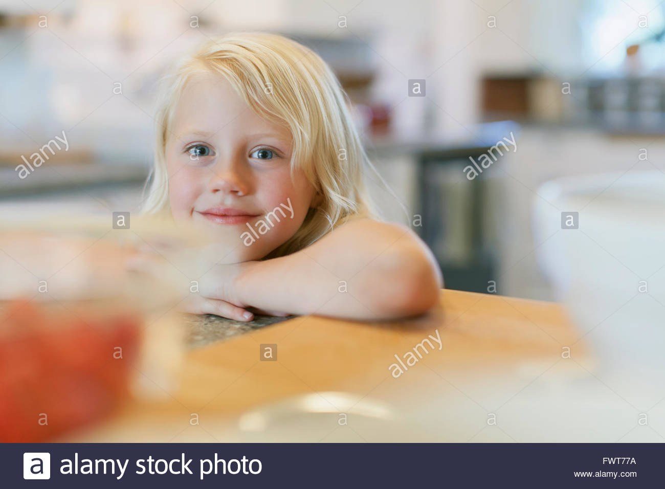 Cute young girl leaning on counter. - Stock Image