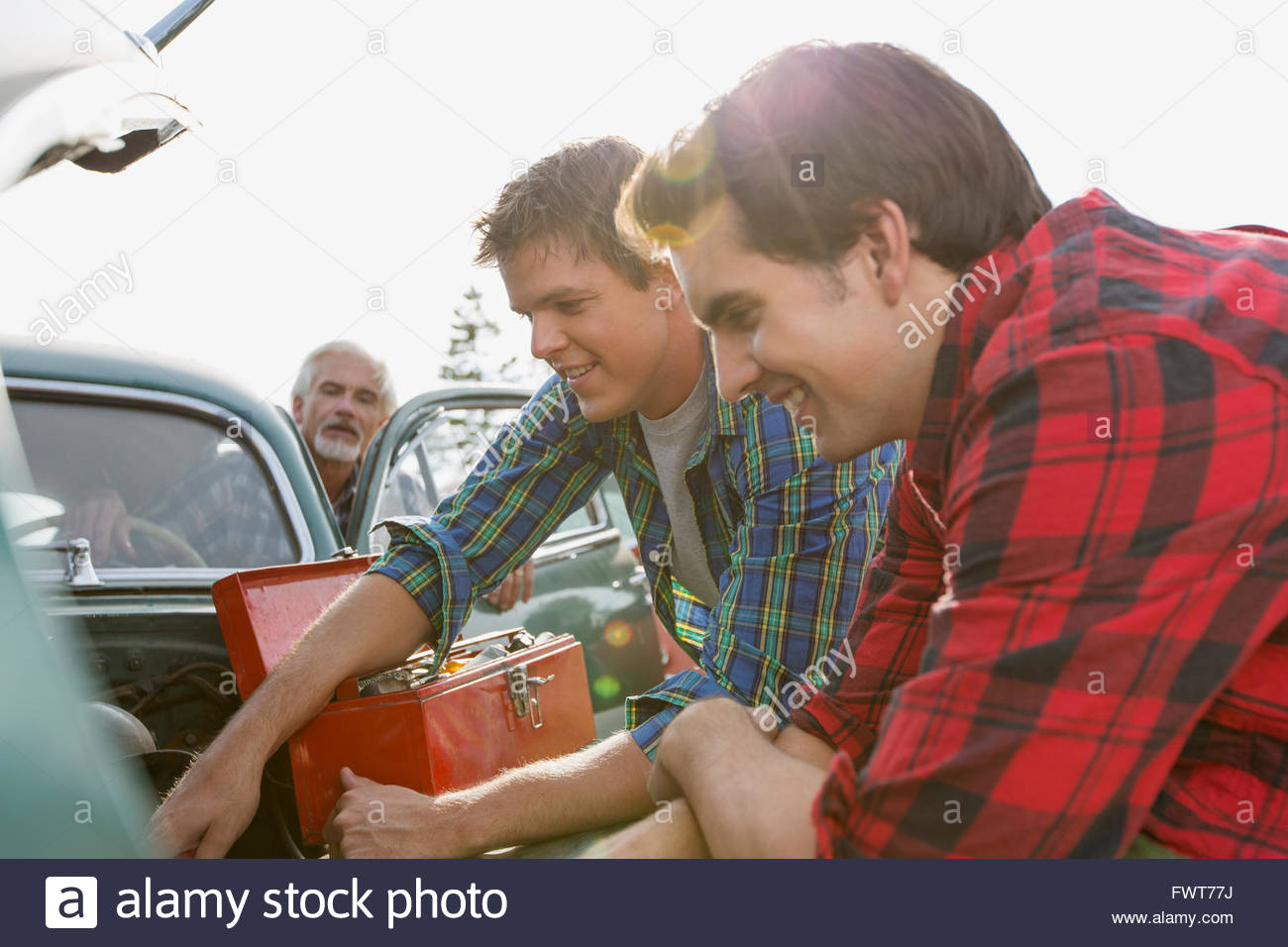 Brothers helping father to repair old car. - Stock Image