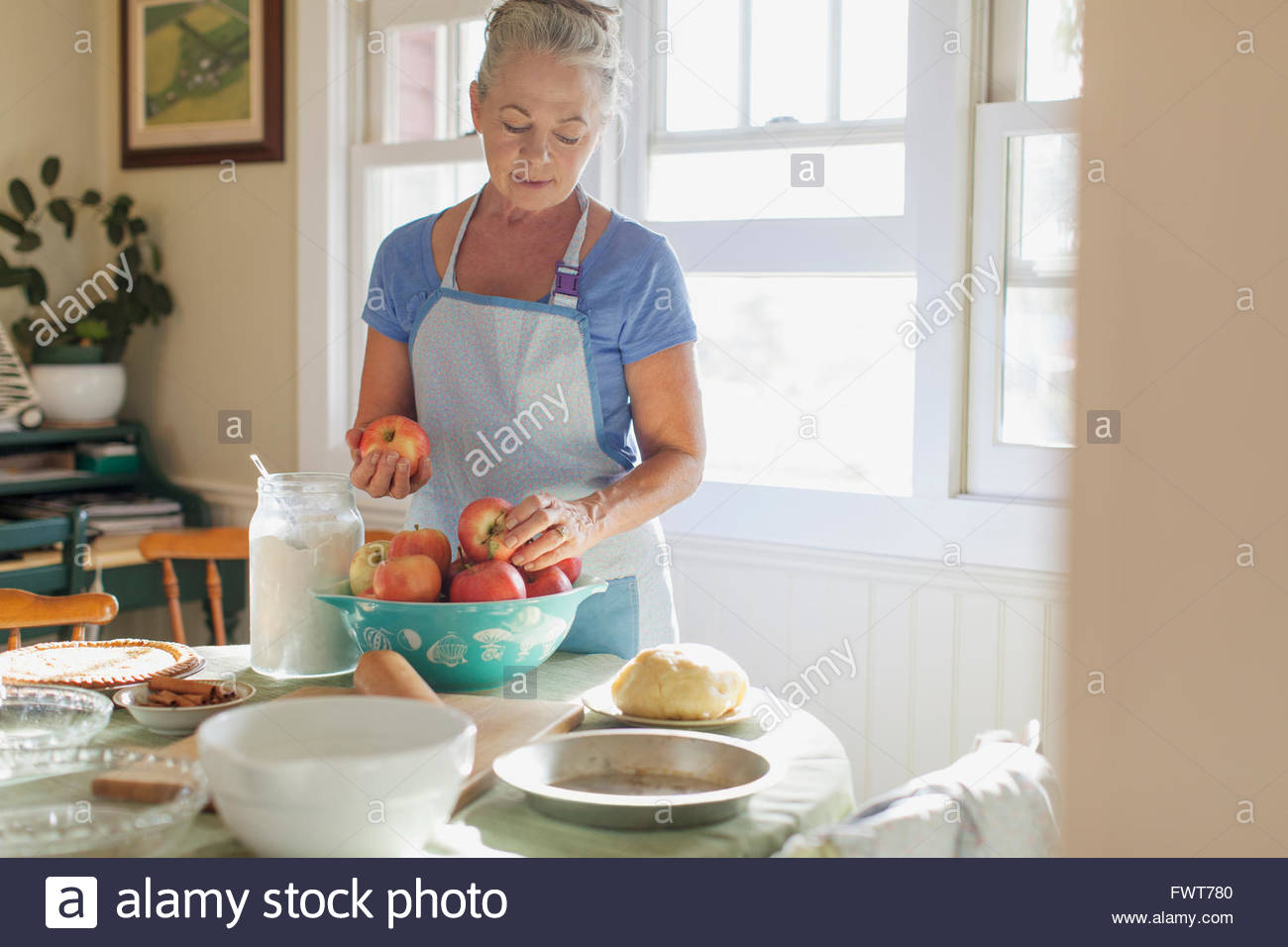 Mature woman in kitchen with apples for pie making. - Stock Image