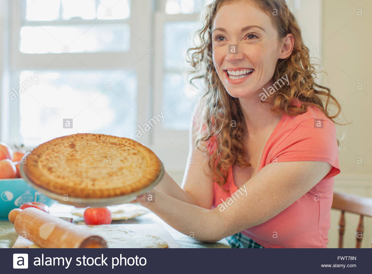 Mid adult woman showing off homemade pie. - Stock Image