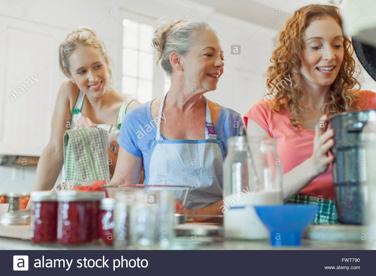 Mother and daughters in kitchen making preserves. - Stock Image