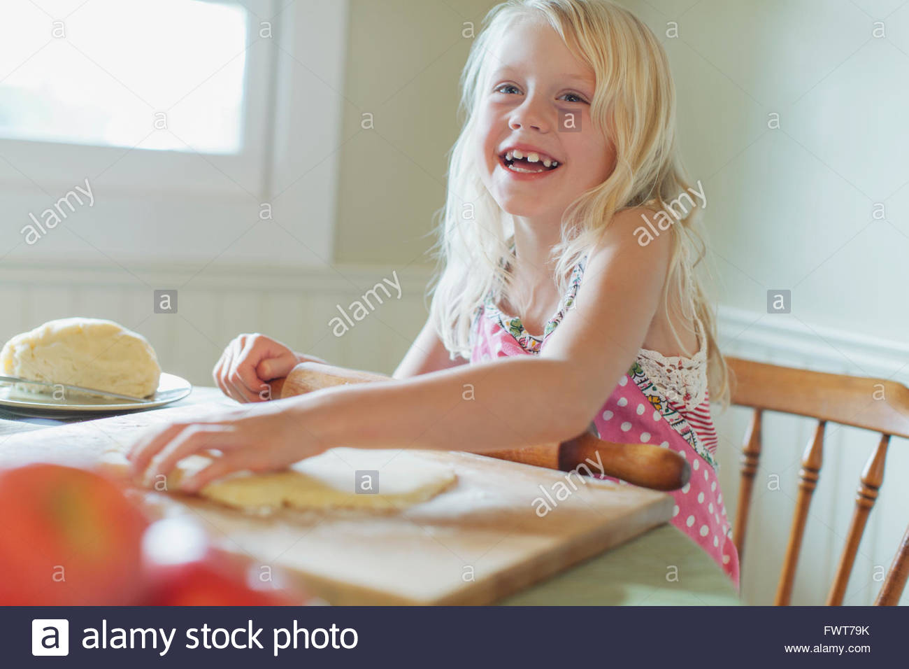 Young girl playing with pie dough. - Stock Image