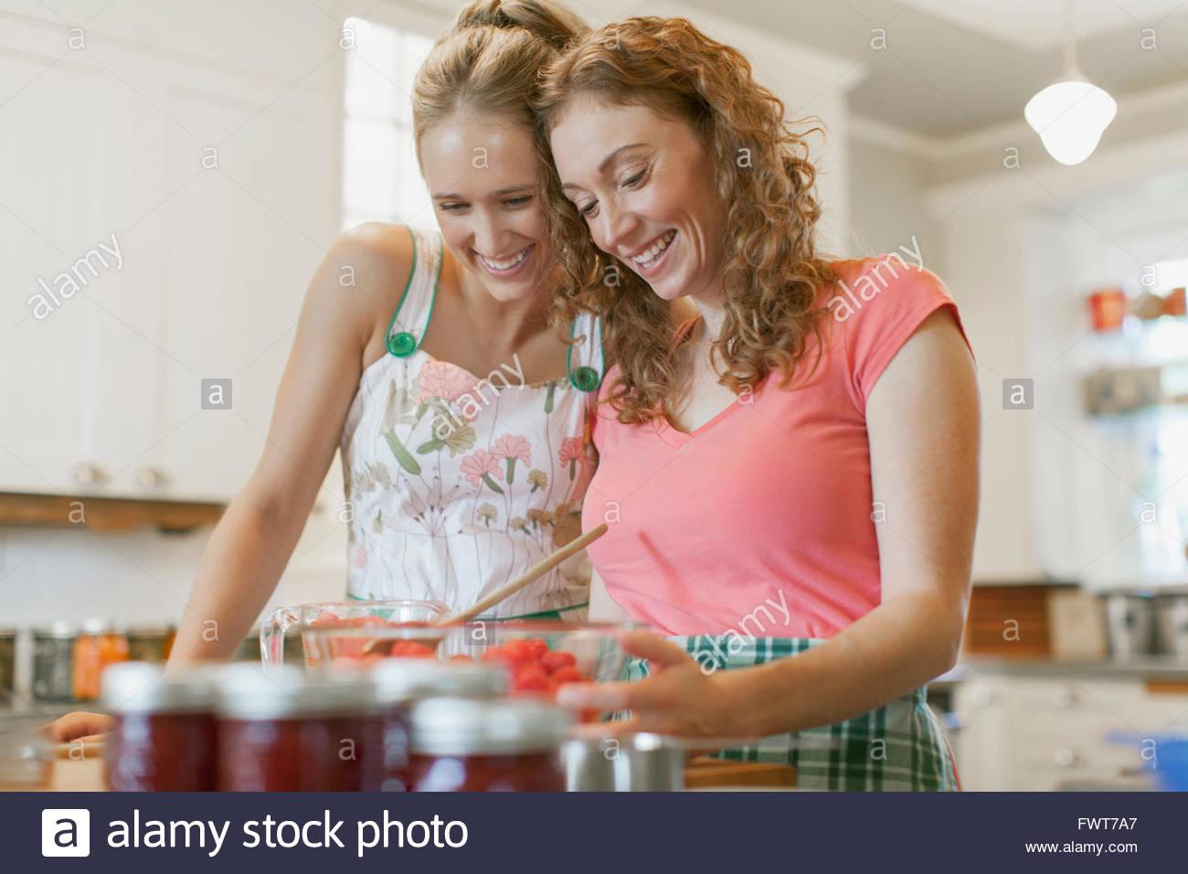 Sisters making fruit jam together. - Stock Image