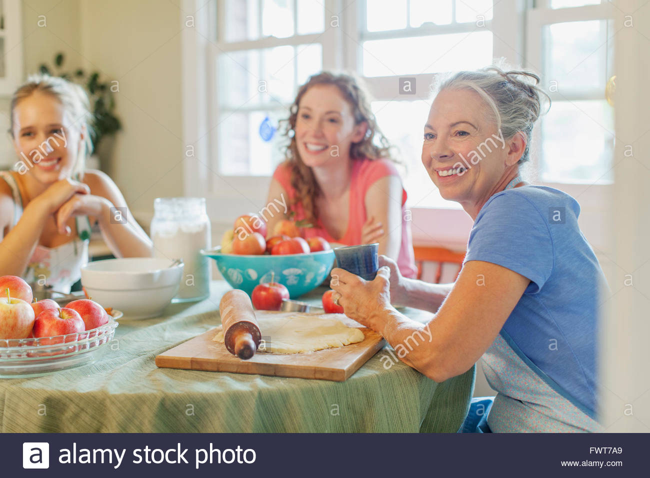Mother and daughters taking a break from making pies. - Stock Image