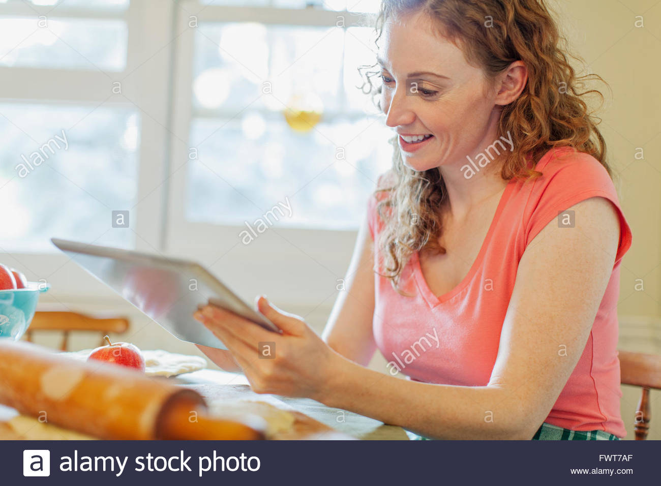 Woman using pc tablet in kitchen. - Stock Image