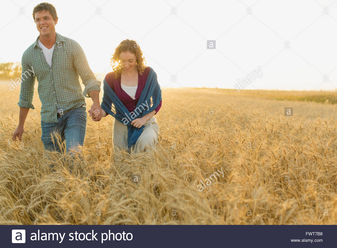 Mid adult couple walking together in wheat field. - Stock Image