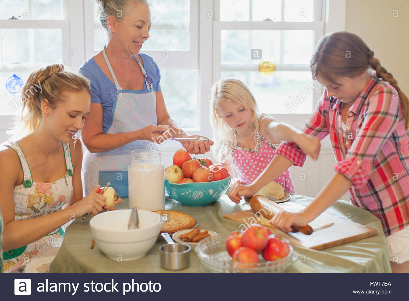 Grandmother supervising granddaughters making pies. - Stock Image