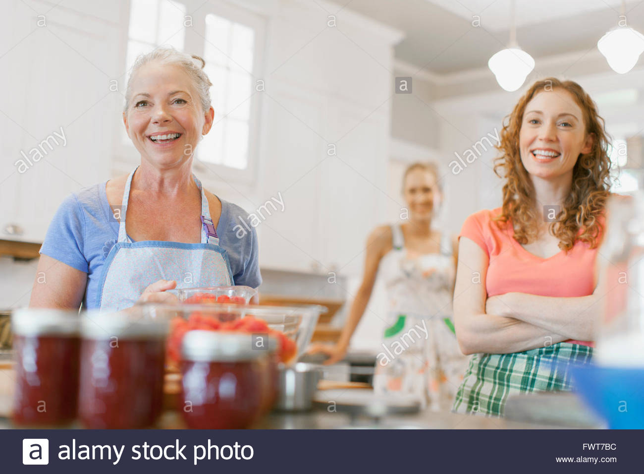 Mother and daughters in kitchen with fruit preserves. - Stock Image