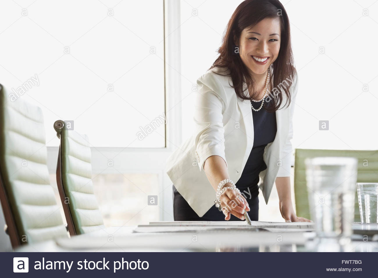 Portrait of businesswoman reviewing blueprint at conference table - Stock Image