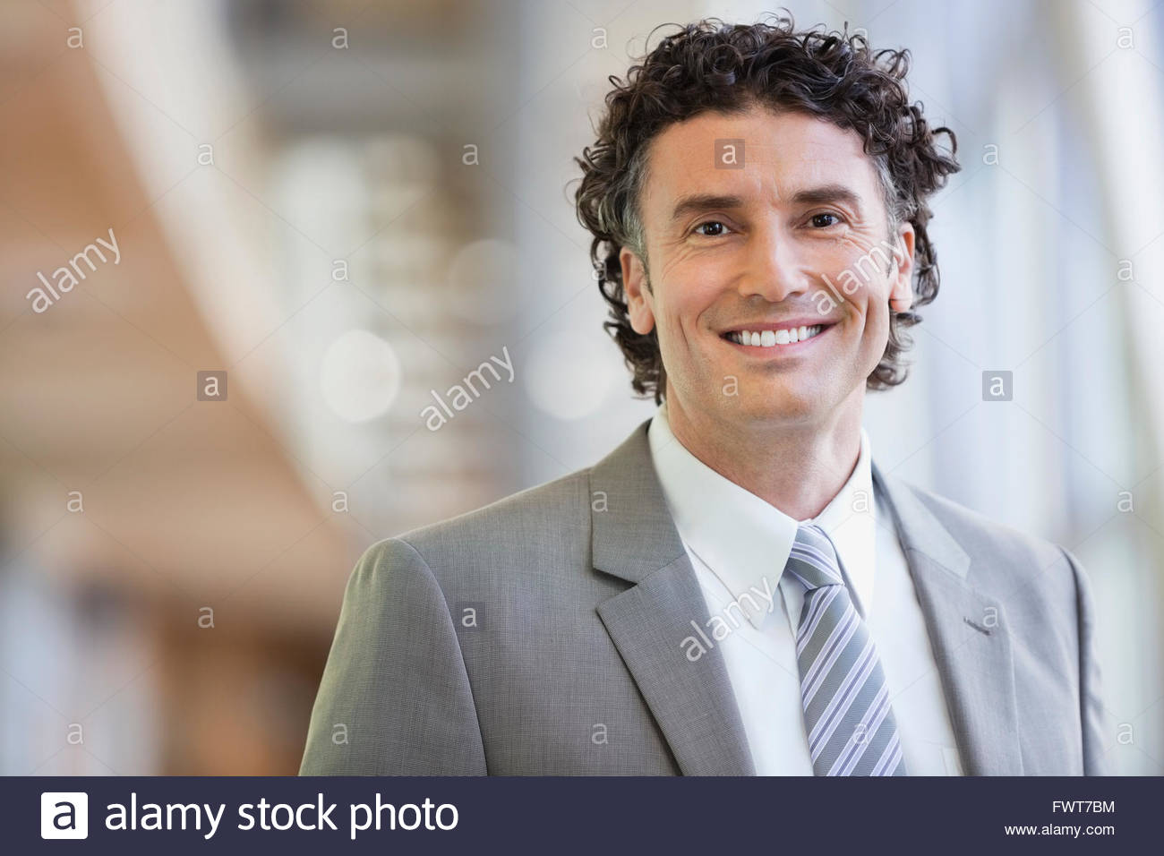 Portrait of mature businessman smiling in office - Stock Image