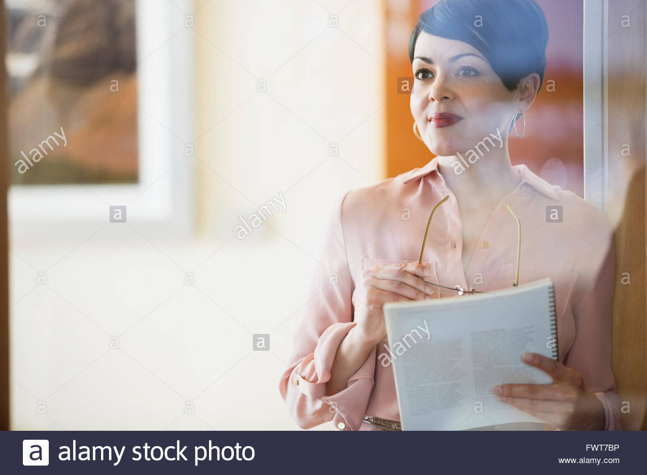 Businesswoman looking away while holding book and eyeglasses - Stock Image