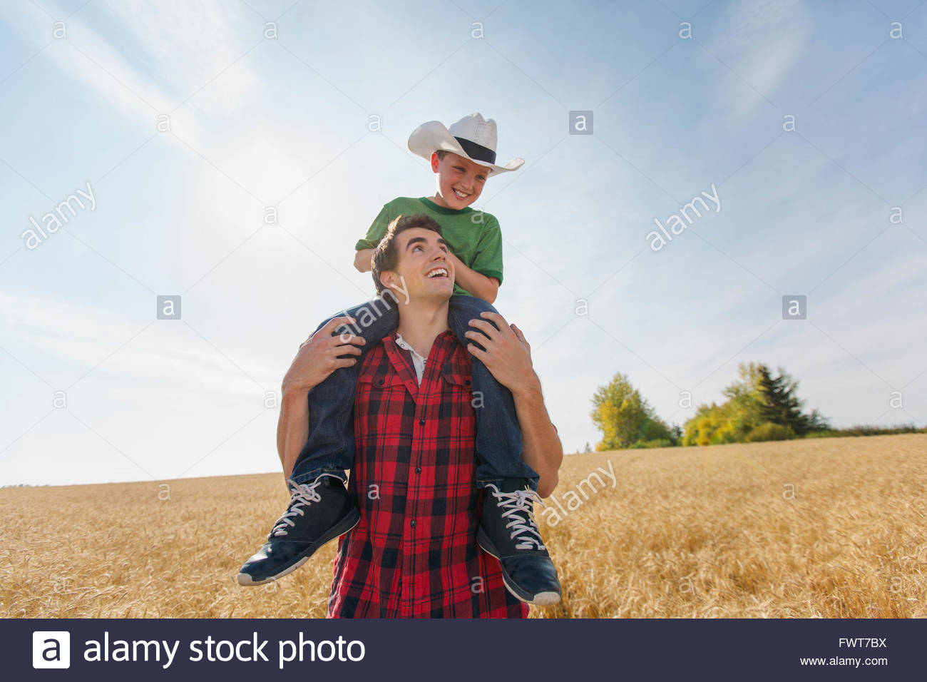 Father giving son piggy-back through wheat field. - Stock Image