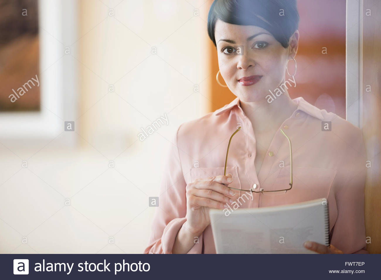 Mature businesswoman holding eyeglasses and notebook in office - Stock Image