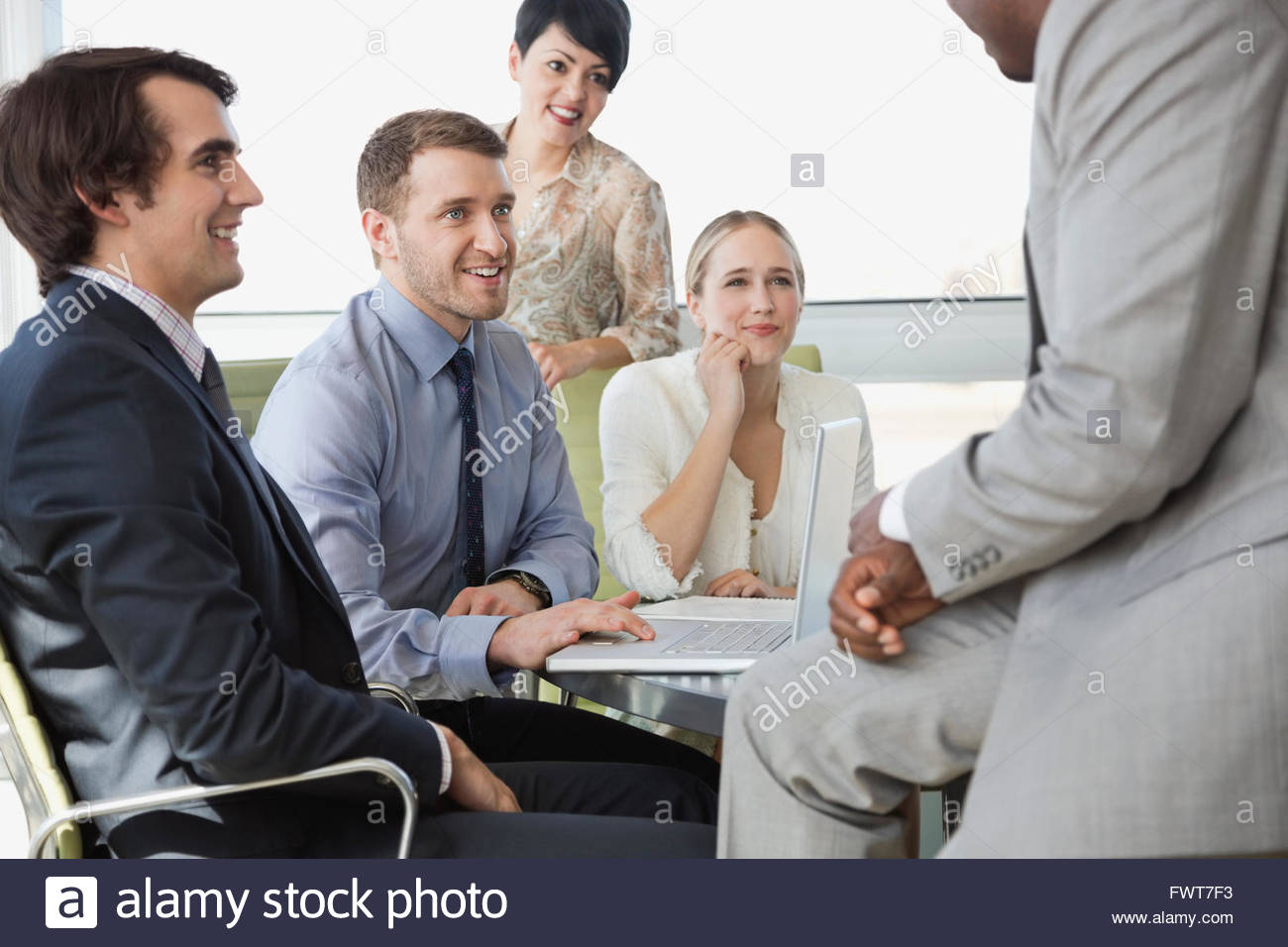 Colleagues looking at leader while sitting in board room - Stock Image