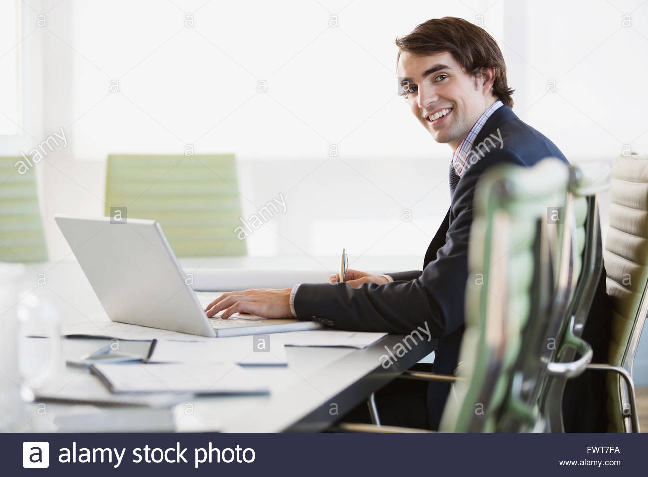 Portrait of young businessman sitting with laptop at conference table - Stock Image
