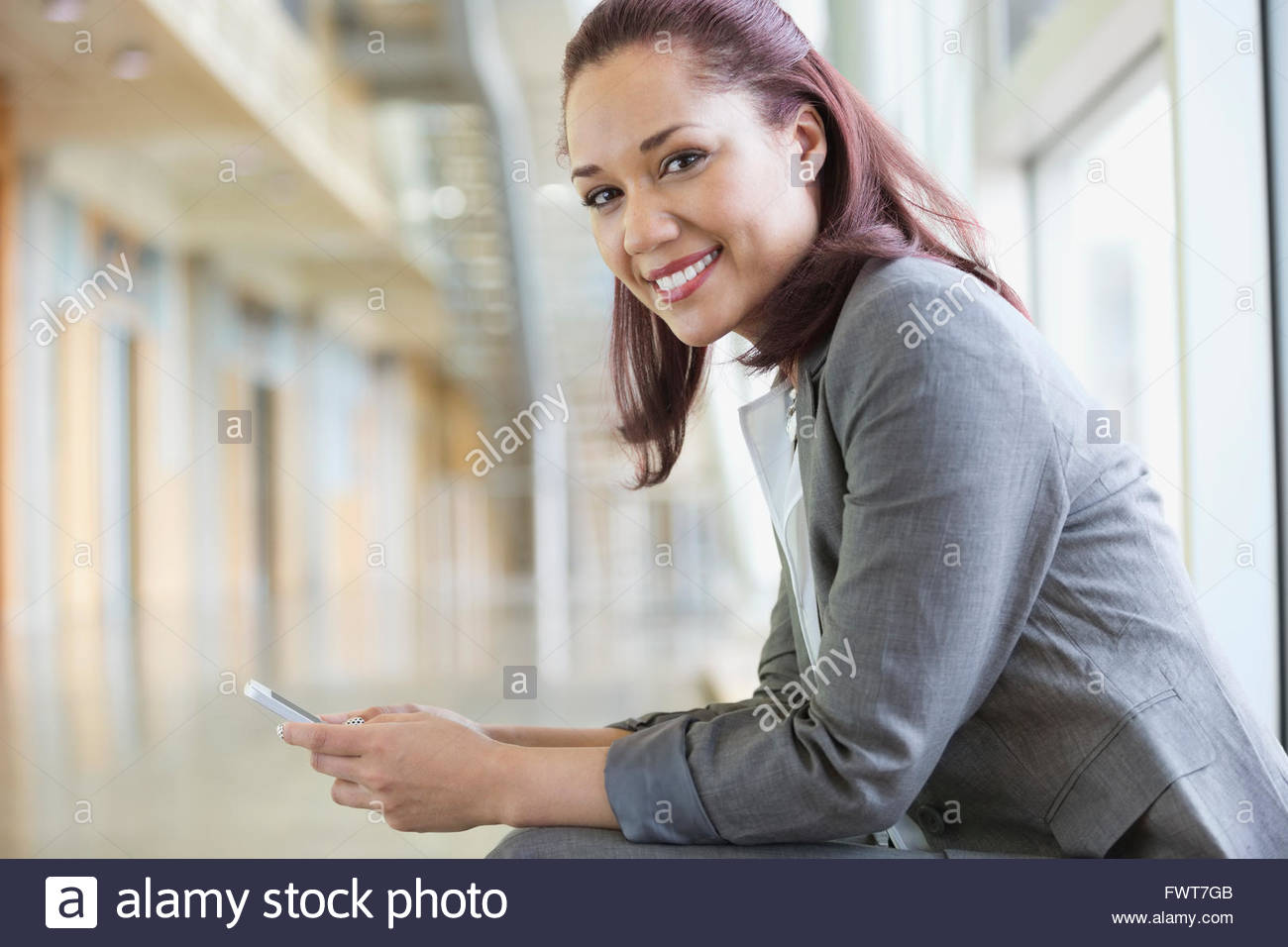 Young businesswoman holding mobile phone in hallway - Stock Image