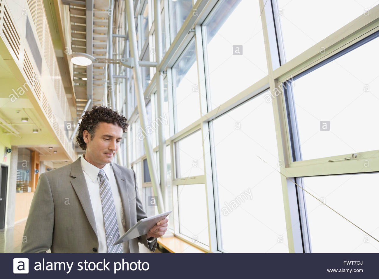 Businessman using digital tablet by windows in office - Stock Image