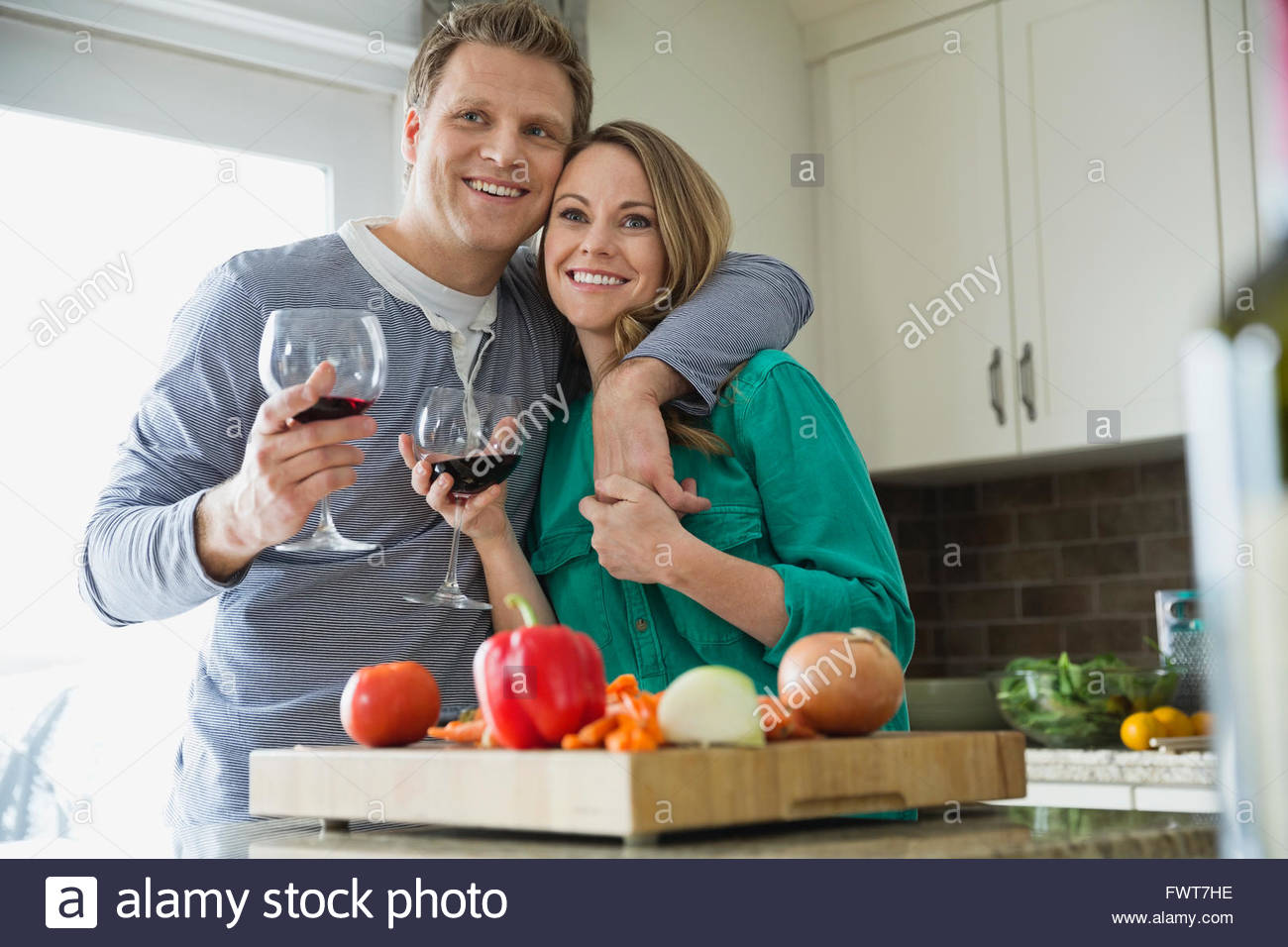 Happy couple enjoying some wine as they prepare dinner - Stock Image