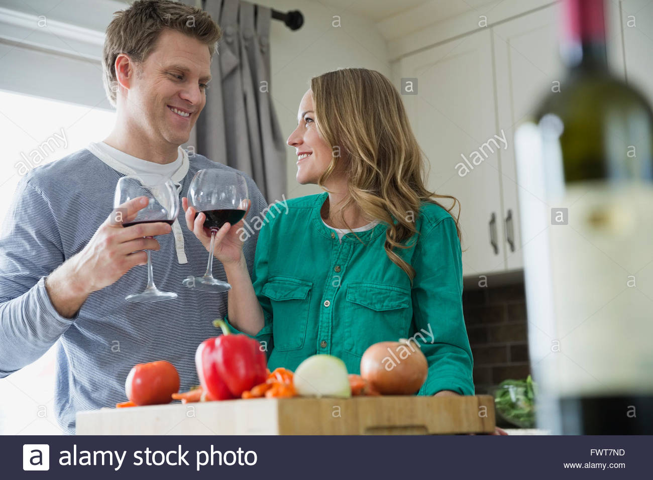 Couple toasting with wine as they prepare dinner. - Stock Image
