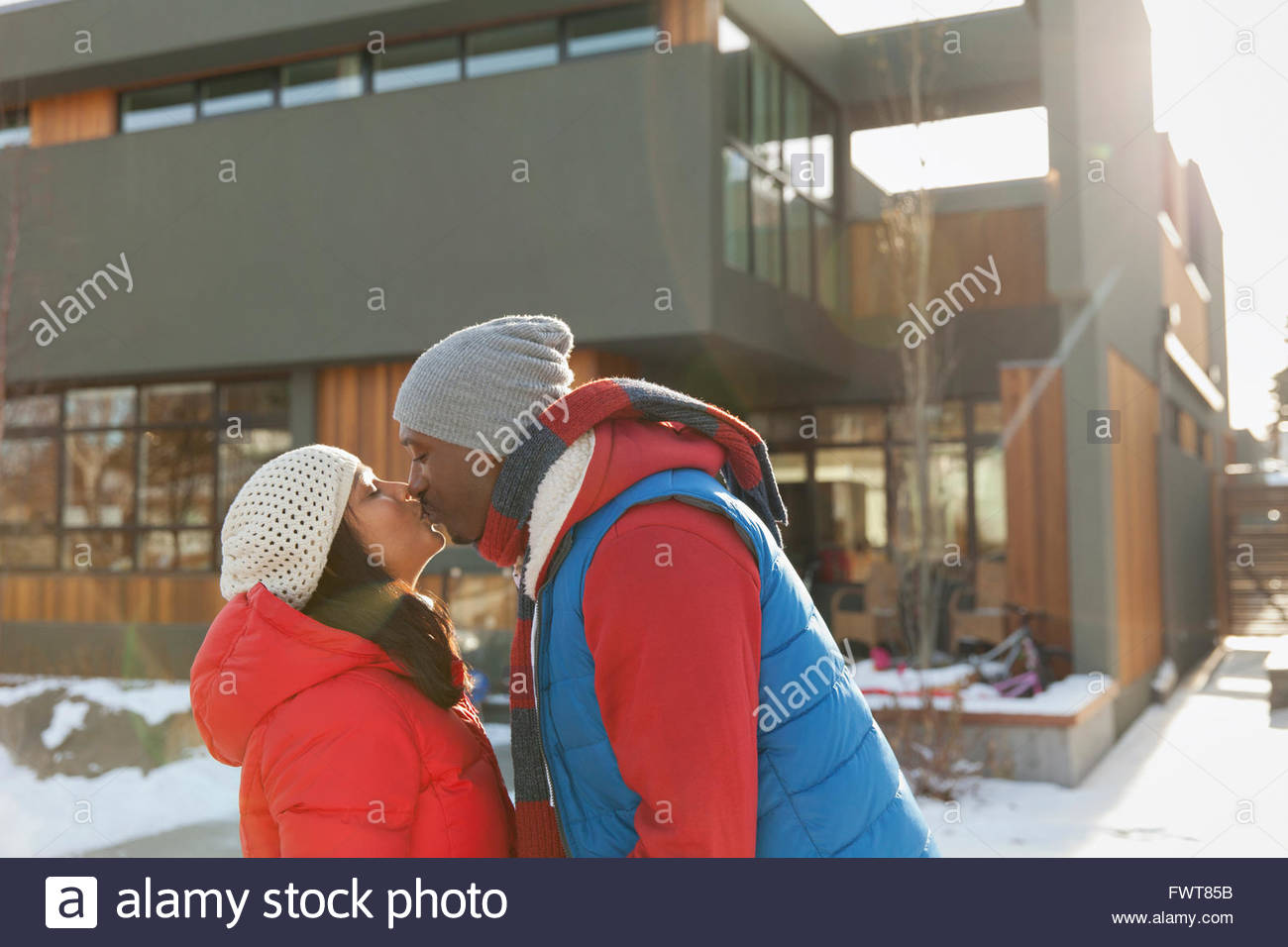 Profile shot of couple kissing outdoors in winter - Stock Image