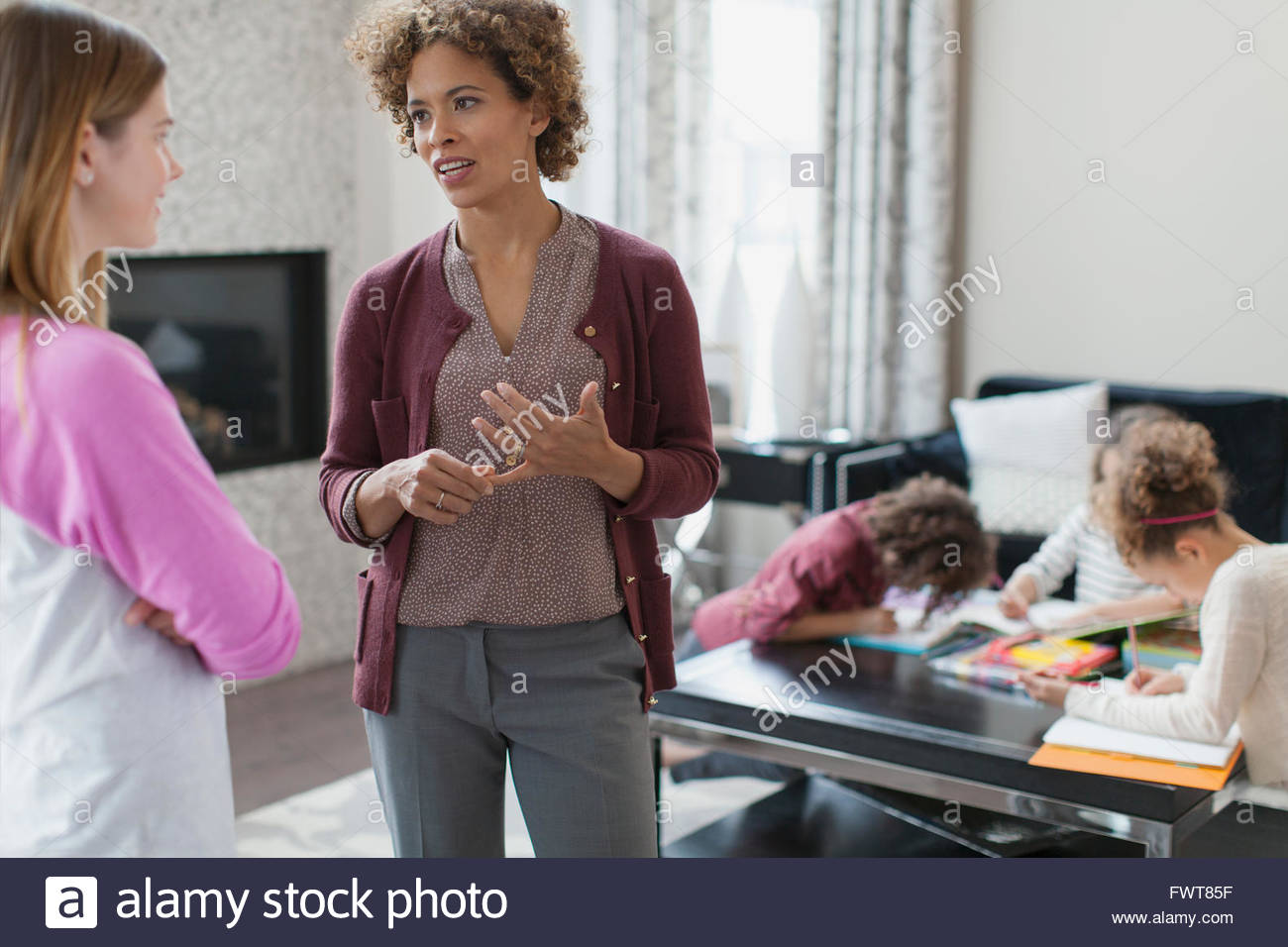 Mother giving instructions to babysitter. - Stock Image