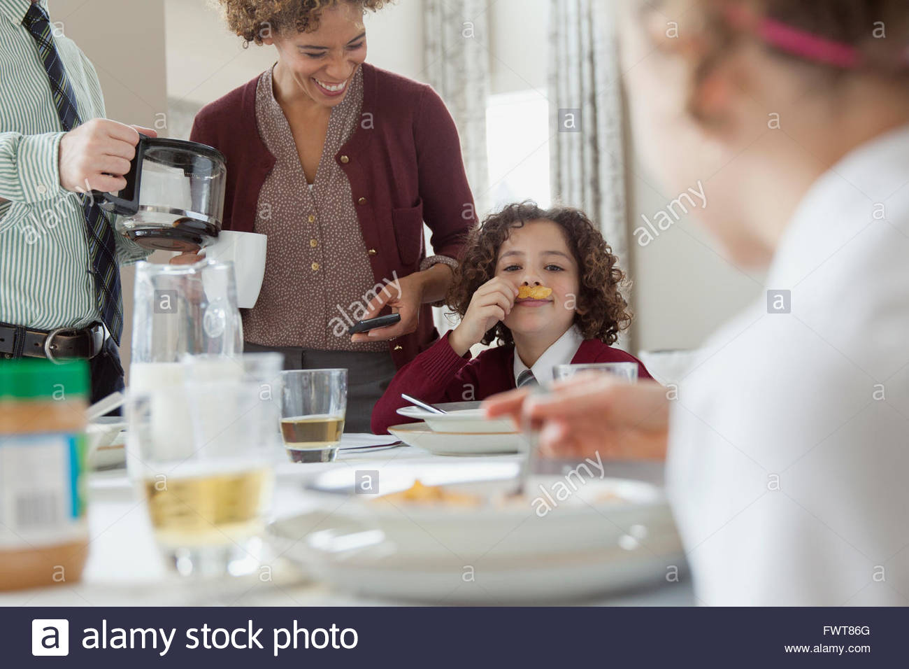 Daughter making a mustache out of cereal flakes at breakfast. - Stock Image