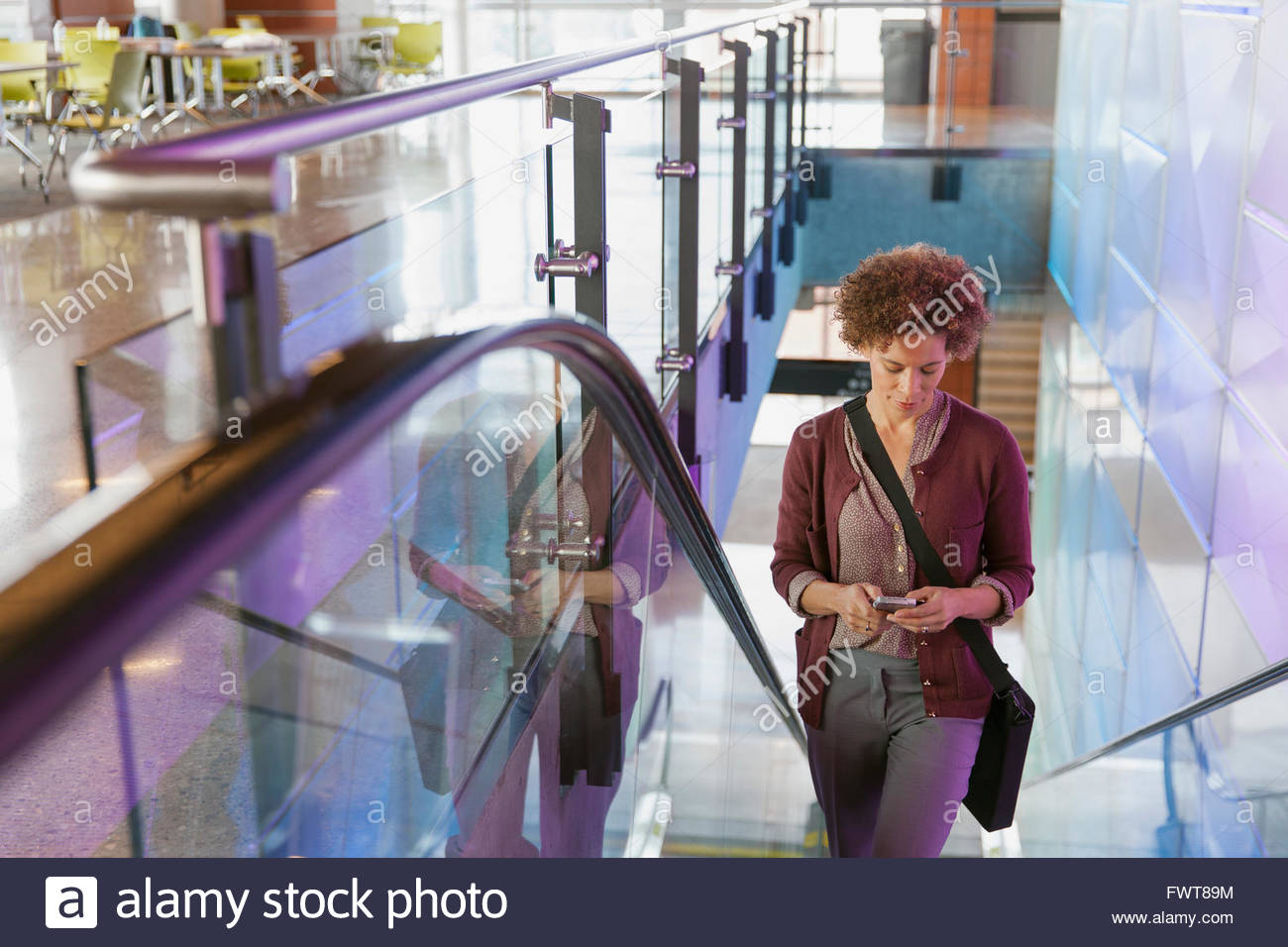 Woman texting on smartphone going up escalator. - Stock Image
