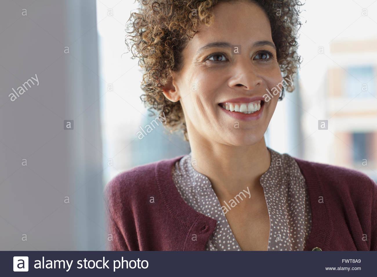Businesswoman smiling at office. - Stock Image