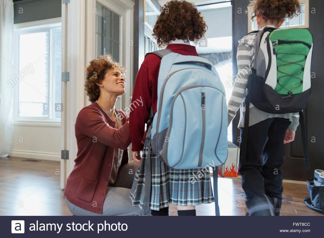 Mother sending daughters off to school. - Stock Image