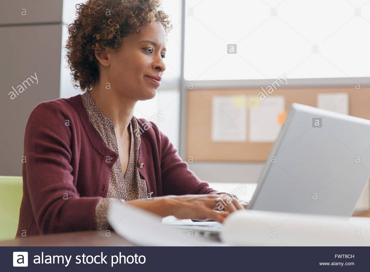 Businessman sitting in caf_ with laptop - Stock Image