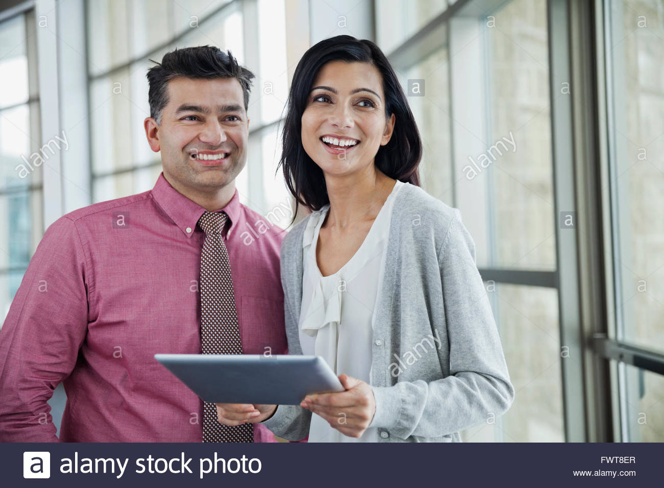 Business people with digital tablet looking away in office - Stock Image