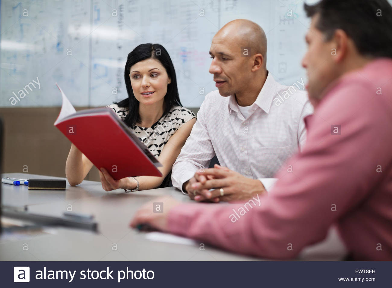 Business people reviewing paperwork in office Stock Photo
