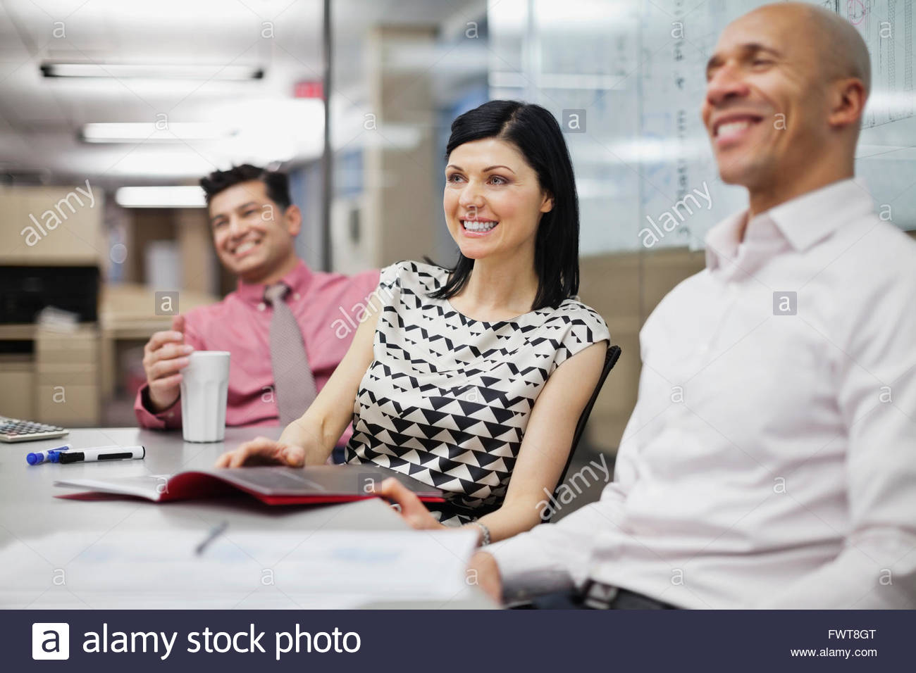Businesswoman with male colleagues in board room Stock Photo